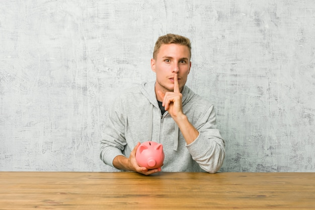 Młody człowiek oszczędzający pieniądze z skarbonką trzymającą w tajemnicy lub proszącą o ciszę.