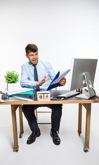 Młody człowiek otrzymuje okropną, szokującą wiadomość. nie może uwierzyć własnym oczom, w szoku traci równowagę, denerwuje się i złości. pojęcie kłopotów pracownika biurowego, biznesu, problemów informacyjnych.