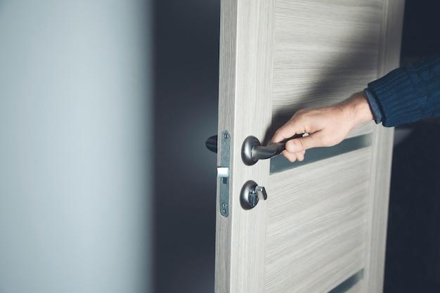 Młody człowiek, otwierając drzwi pokoju
