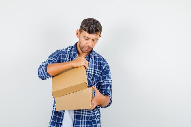 Młody człowiek, otwierając karton w koszuli i patrząc ostrożnie, widok z przodu.