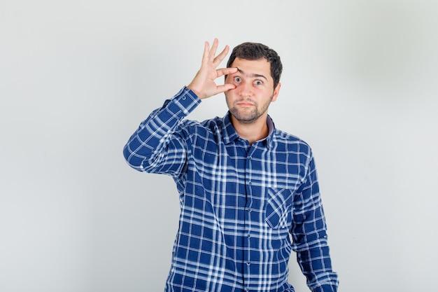 Młody człowiek otwierając oko palcami w kraciastej koszuli