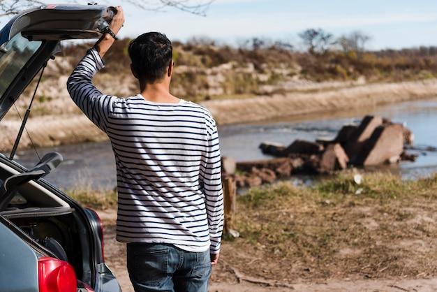 Młody człowiek outdoors patrzeje daleko od