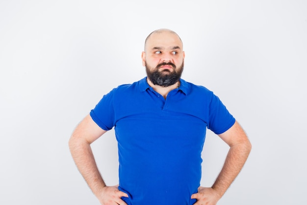 Młody człowiek patrząc na bok z rękami w talii w niebieskiej koszuli i patrząc niezadowolony. przedni widok.