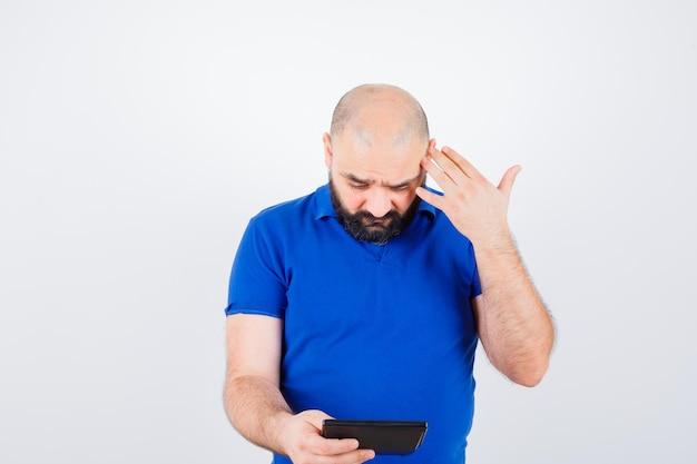 Młody człowiek patrząc na kalkulator, myśląc w niebieskiej koszuli i patrząc skupiony. przedni widok.