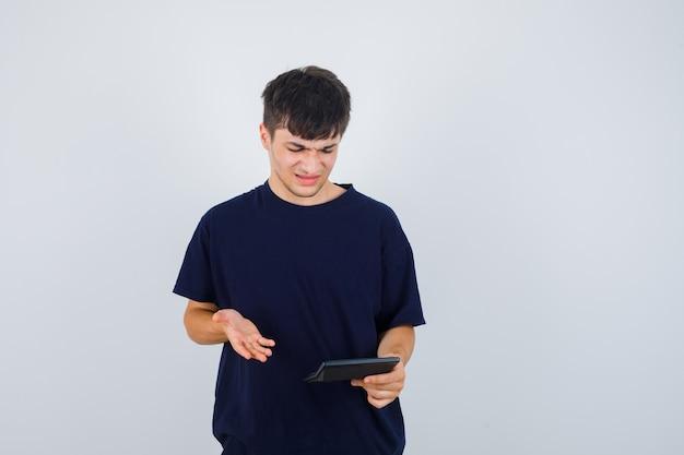 Młody człowiek patrząc na kalkulator w czarnej koszulce i wyglądający na zdezorientowanego. przedni widok.