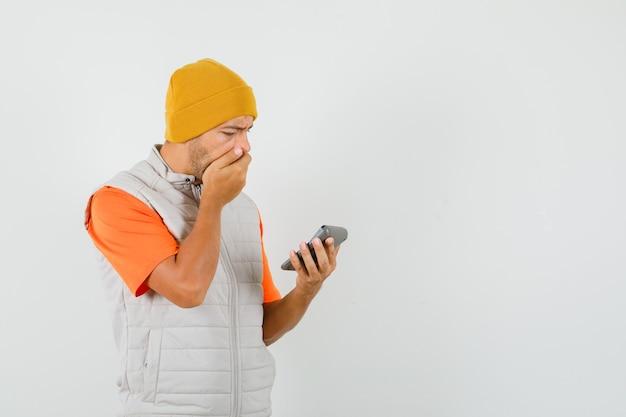 Młody człowiek patrząc na kalkulator w t-shirt, kurtkę, kapelusz i niespokojny widok z przodu.