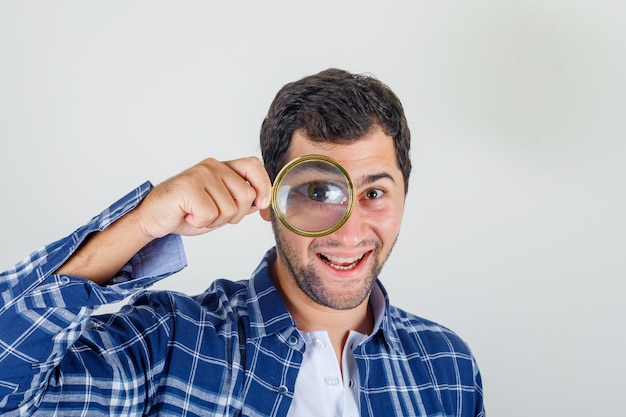 Młody człowiek patrząc na kamery przez szkło powiększające w koszuli i patrząc szczęśliwy