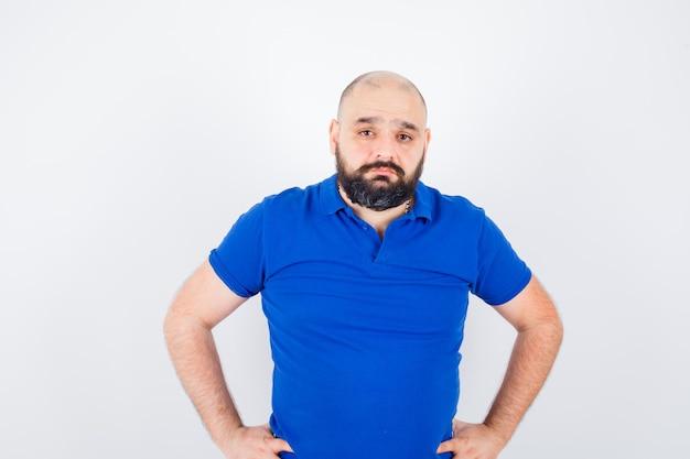 Młody człowiek patrząc na kamery ręką na pasie w niebieskiej koszuli, widok z przodu.