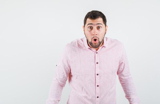 Młody człowiek patrząc na kamery w różowej koszuli i patrząc zszokowany