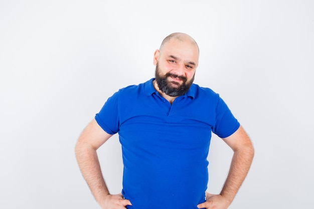 Młody człowiek patrząc na kamery z rękami w talii, uśmiechając się w niebieskiej koszuli i patrząc zadowolony. przedni widok.