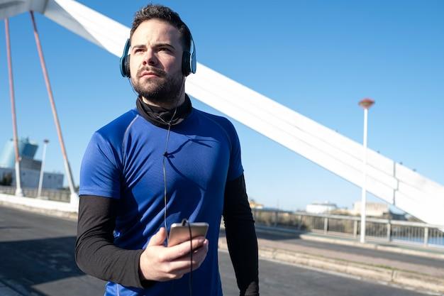Młody człowiek, patrząc na swój telefon komórkowy, aby słuchać muzyki podczas biegania przez obszar miejski