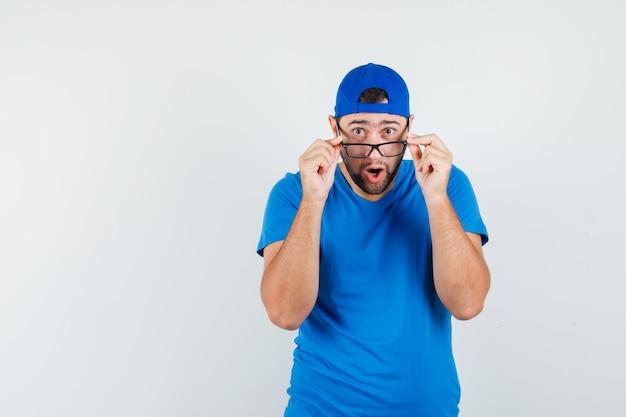 Młody człowiek patrząc przez okulary w niebieskiej koszulce i czapce i wyglądający na zszokowanego