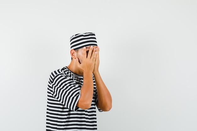 Młody człowiek patrząc przez palce w kapeluszu t-shirt w paski i wyglądający na przestraszonego