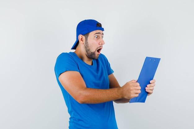 Młody człowiek patrząc przez schowek w niebieskiej koszulce i czapce i patrząc zszokowany
