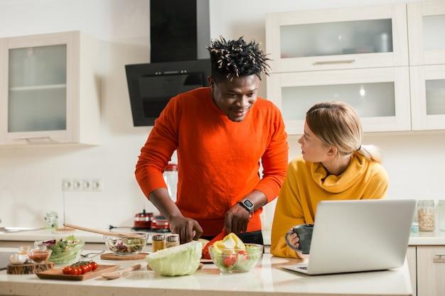 Młody człowiek, patrząc uważnie na ekran nowoczesnego laptopa podczas krojenia warzyw ze swoją ciekawą dziewczyną stojącą w pobliżu
