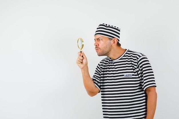 Młody człowiek, patrząc uważnie przez szkło powiększające w pasiastym t-shirt kapeluszu