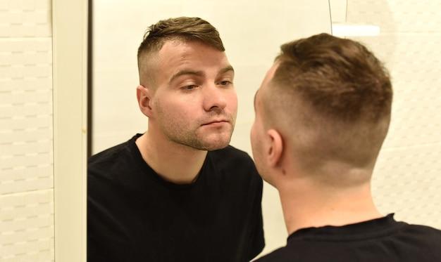 Młody człowiek patrząc w lustro na swoje odbicie w łazience