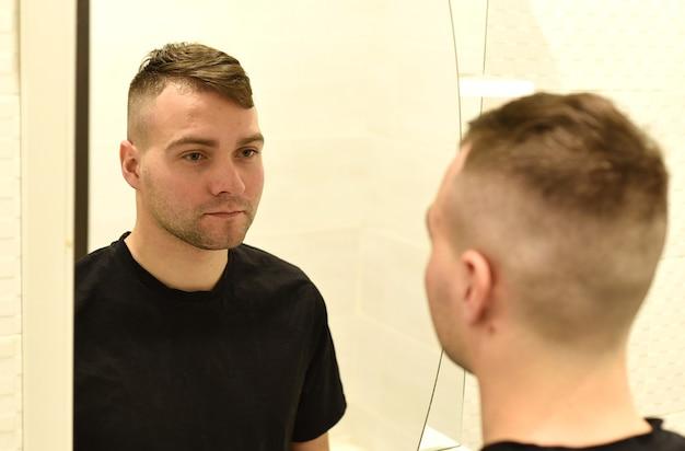 Młody człowiek patrząc w lustro na swoje odbicie