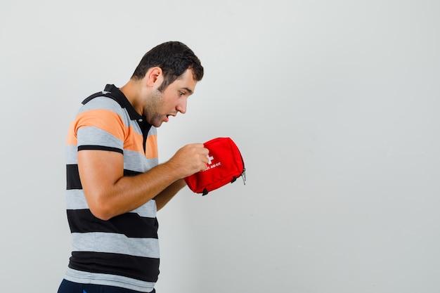 Młody człowiek patrząc wewnątrz apteczki w t-shirt i wyglądający na zainteresowany.