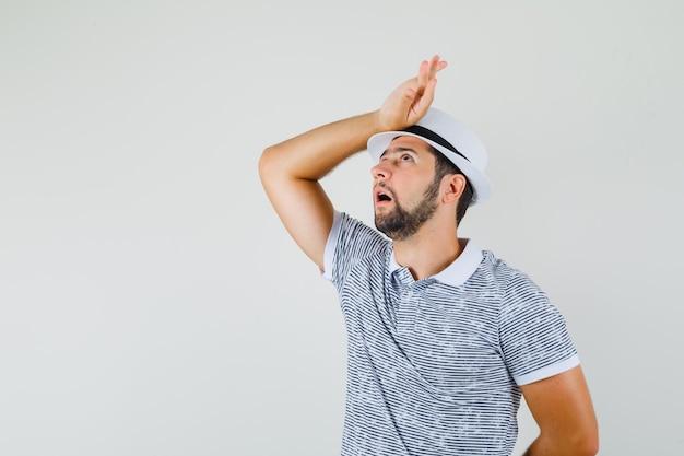 Młody człowiek patrząc z ręką na głowie w t-shirt, kapelusz i patrząc zamyślony, widok z przodu.