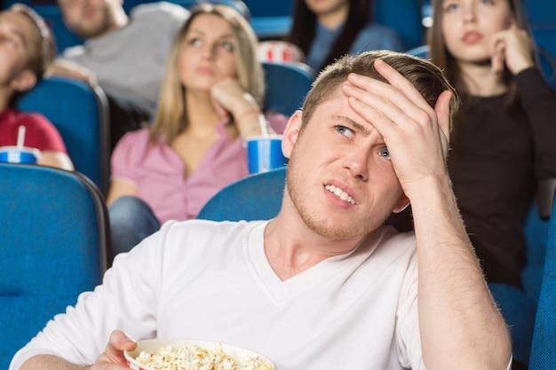 Młody człowiek patrząc zirytowany, robiąc facepalm oglądając filmy w kinie
