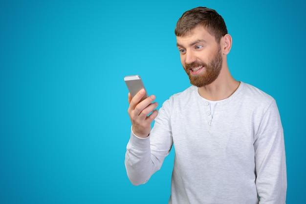 Młody człowiek patrzeje jego smartphone