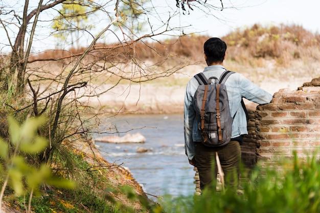 Młody człowiek patrzeje jezioro z plecakiem