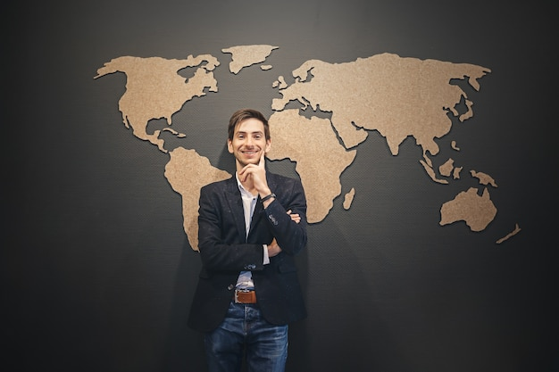 Młody człowiek patrzeje mapa świata ze skrzyżowanymi rękami