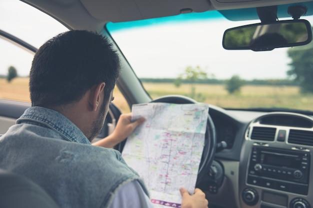 Młody człowiek patrzeje mapę w samochodzie