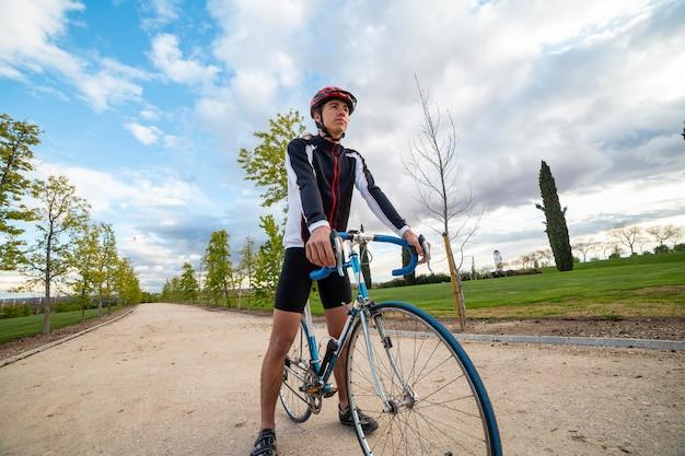 Młody człowiek patrzeje odległość i myśleć o nieskończoności w hełmie i sportswear podczas gdy stojący na wsi drodze z bicyklem przeciw chmurnemu niebu
