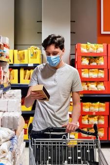 Młody człowiek patrzeje przekąski w supermarkecie z maską