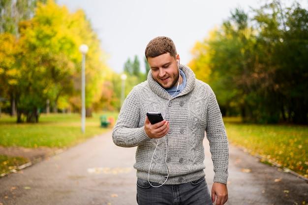 Młody człowiek patrzeje smartphone z słuchawkami