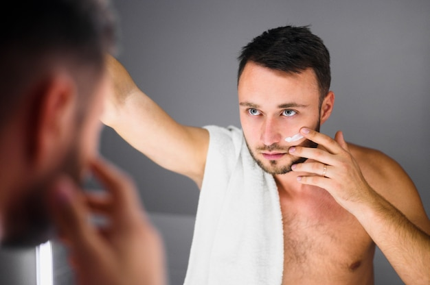 Młody człowiek patrzeje w lustrze z ręcznikiem na jego ramieniu