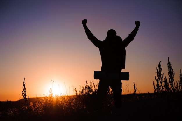 Młody człowiek patrzy na zachód słońca, podróżnik z plecakiem