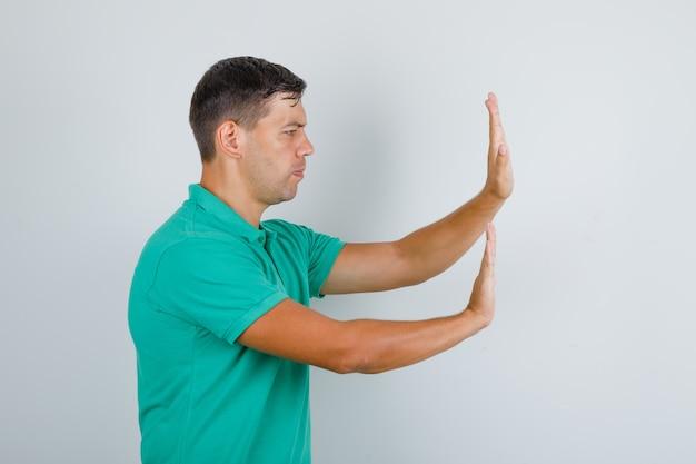Młody człowiek pcha coś rękami w zielonej koszulce i wygląda poważnie. .