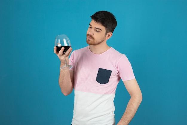 Młody człowiek pewnie trzyma kieliszek wina i patrząc na to.