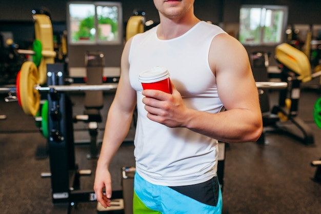 Młody człowiek pić kawę po ćwiczeniach