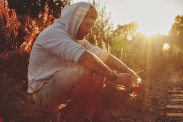 Młody człowiek pije alkohol na opuszczonej linii kolejowej na wsi o zachodzie słońca. pojęcie smutku, apatii, depresji lub nieprawidłowego stylu życia. skopiuj miejsce