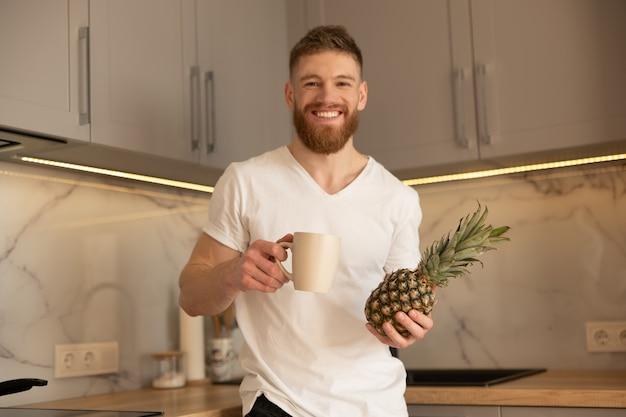 Młody człowiek pije herbatę lub kawę z kubka i trzyma ananasa w kuchni w domu. przystojny europejski brodaty facet patrząc na kamery. wnętrze nowoczesnego mieszkania. dzień
