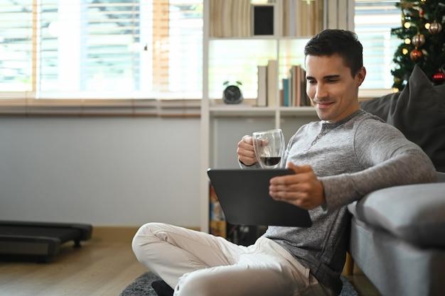 Młody człowiek pije kawę i przegląda internet na cyfrowym tablecie.