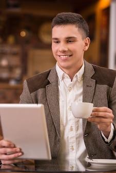 Młody człowiek pije kawę i używa pastylka komputer w kawiarni.