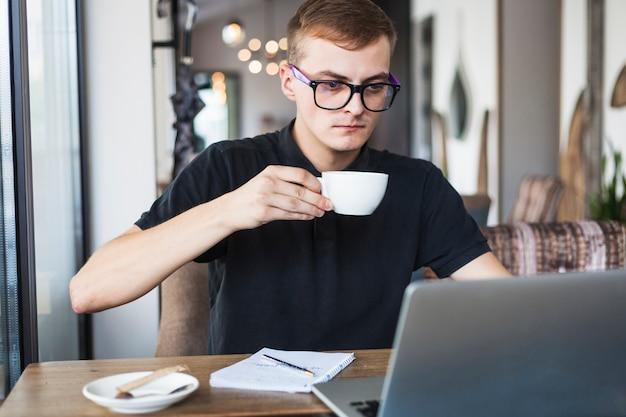 Młody człowiek pije kawę przy stołem z laptopem