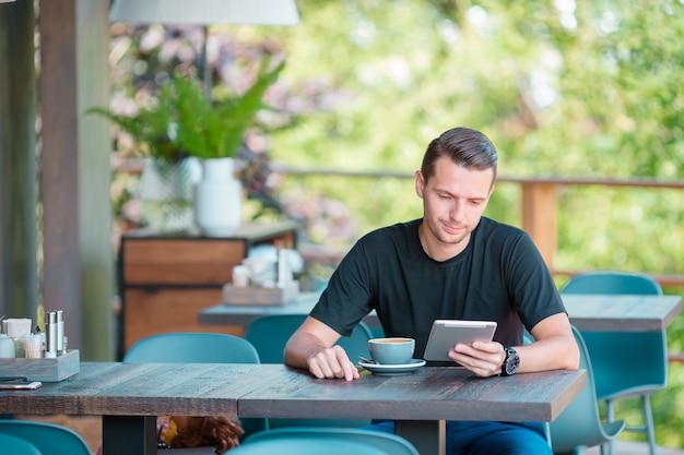 Młody człowiek pije kawę z laptopem w plenerowej kawiarni. człowiek za pomocą smartfona.