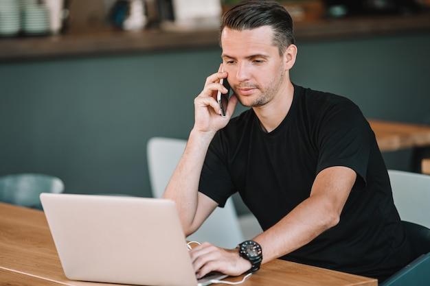Młody człowiek pije kawę z laptopem w plenerowej kawiarni.