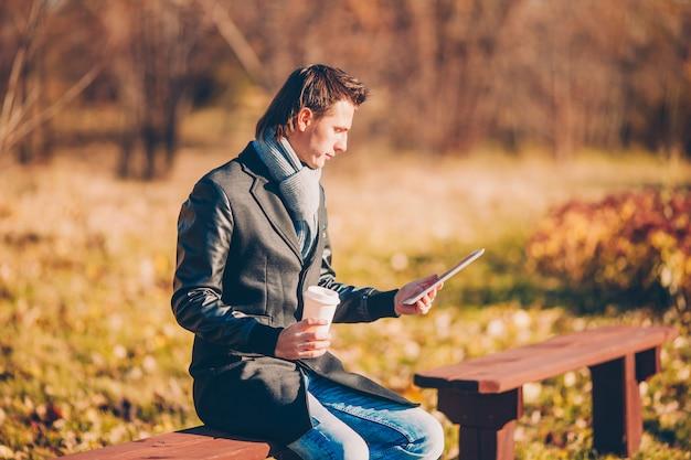 Młody człowiek pije kawę z telefonem w jesień parku outdoors