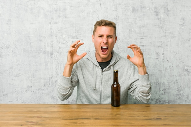 Młody człowiek pije piwo na stole krzyczy z wściekłości.