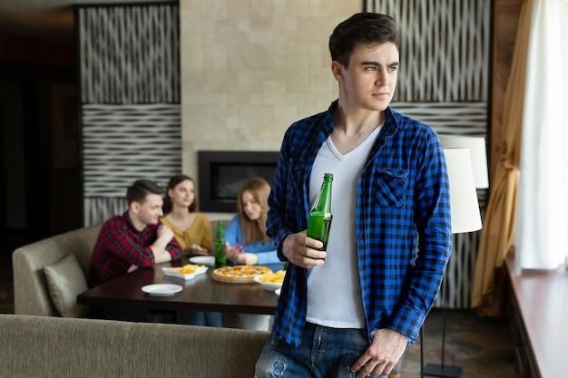 Młody człowiek pije piwo z butelki i wygląda przez okno w kawiarni