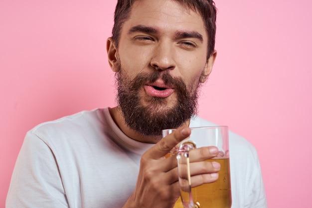 Młody człowiek pije piwo ze szklanki