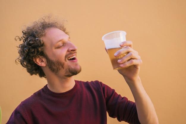 Młody człowiek pije piwo.