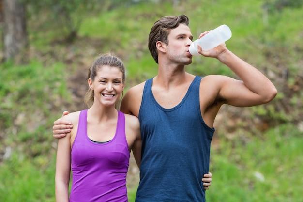 Młody człowiek pije podczas gdy stojący z kobietą
